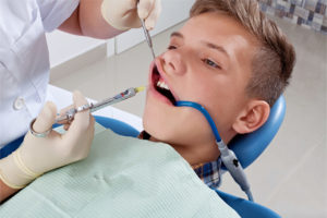 injection to boy patient for light sedation before tooth filling